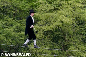 Chris Bull, 37, walks on a high wire at Wookey Hole Caves near Wells, Somerset, England. May 1 2015. Chris Bull, 37, and Phoebe Baker, 25, got married in the caves having both walked the high wire, meeting in the middle. See SWNS copy SWWIRE : This is the moment a couple took their romance to new heights by exchanging vows - on a tightrope 25 metres off the ground. Chris Bull - in full morning suit - and Phoebe Baker - in a flowing white wedding dress - started from opposite ends of the 75 metre-long highwire before meeting in the middle. They then said 'I do' over the heads of around 100 friends and family watching on from the ground at Wookey Hole in Somerset. The event - billed as the UK's first-ever highwire wedding - was always on the cards for the daredevil couple. Chris, 37, a professional rope walker, fell for Chloe, 25, at a circus show where she was a costume designer.
