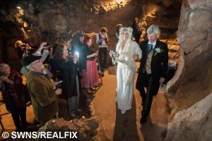 Bride Phoebe Baker, 25, walks alongside her father into a chamber at Wookey Hole Caves near Wells, Somerset, England. May 1 2015. Chris Bull, 37, and Phoebe Baker, 25, got married in the caves having both walked the high wire, meeting in the middle.  See SWNS copy SWWIRE : This is the moment a couple took their romance to new heights by exchanging vows - on a tightrope 25 metres off the ground. Chris Bull - in full morning suit - and Phoebe Baker - in a flowing white wedding dress - started from opposite ends of the 75 metre-long highwire before meeting in the middle. They then said 'I do' over the heads of around 100 friends and family watching on from the ground at Wookey Hole in Somerset. The event - billed as the UK's first-ever highwire wedding - was always on the cards for the daredevil couple. Chris, 37, a professional rope walker, fell for Chloe, 25, at a circus show where she was a costume designer.