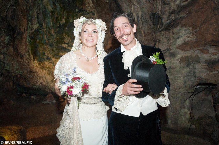 Newlyweds Phoebe Baker, 25, (left) and Chris Bull, 37, (right) pose for a portrait after their wedding ceremony in Wookey Hole Caves near Wells, Somerset, England. May 1 2015. Chris Bull, 37, and Phoebe Baker, 25, got married in the caves having both walked the high wire, meeting in the middle.  See SWNS copy SWWIRE : This is the moment a couple took their romance to new heights by exchanging vows - on a tightrope 25 metres off the ground. Chris Bull - in full morning suit - and Phoebe Baker - in a flowing white wedding dress - started from opposite ends of the 75 metre-long highwire before meeting in the middle. They then said 'I do' over the heads of around 100 friends and family watching on from the ground at Wookey Hole in Somerset. The event - billed as the UK's first-ever highwire wedding - was always on the cards for the daredevil couple. Chris, 37, a professional rope walker, fell for Chloe, 25, at a circus show where she was a costume designer.