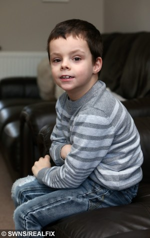 Alfie Smith, 7, is pictured at hs home in Awsworth, Nottinghamshire on January 26 2015.  Little Alfie Smith is desperate to play football with his friends – but he suffers from a rare condition that means eating a burger or even drinking too much milk could damage his brain.  See NTI story NTIBURGER.  The seven-year-old is allergic to protein, which has stunted his development – leaving him unable to feed himself, walk or control his movements.  His parents are now desperately trying to raise £18,000 to fund pioneering treatment abroad which could help Alfie learn to walk. The genetic condition, called Glutaric Acidemia type 1, means the youngster's brain can be damaged if he eats more than 19g of protein a day – about three eggs, a small chicken breast or a pint of milk.  It means things that normal children enjoy – such as a quarter-pounder burger – are off the menu and instead Alfie has to fill up on plates of cabbage and carrots.  Last year he had an eight-hour operation in London to insert electrodes into his brain and a battery pack put into his stomach to cut down his involuntary movements by helping his brain to communicate with his limbs.  His family, from Awsworth, now want to take him to a specialist clinic in Slovakia for a type of physiotherapy which is unavailable on the NHS.