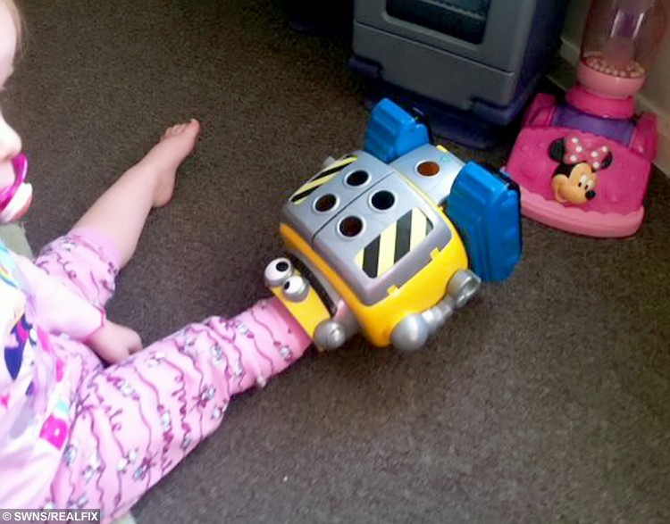 Darcie with her foot trapped in the toy.  This is the dramatic moment firefighters had to rescue a two-year-old girl after she got her foot stuck in a MINION robot.  See NTI story NTIMINION.  Toddler Darcie Butler was playing with her favourite toy at 6.30am yesterday morning (Thur) when she got her leg wedged in the £40 machine.  Her mum Claire Tooth, 29, and dad Steve Butler, 38, tried to yank her foot out but were forced to call their local fire station when it wouldn't budge.  Firefighters rushed round to their home in Oldbury, West Mids., and used a hand saw to cut the robot in half in order to free brave Darcie.