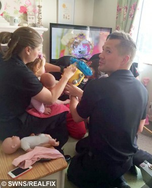 Fire crews attend to Darcie.  This is the dramatic moment firefighters had to rescue a two-year-old girl after she got her foot stuck in a MINION robot.  See NTI story NTIMINION.  Toddler Darcie Butler was playing with her favourite toy at 6.30am yesterday morning (Thur) when she got her leg wedged in the £40 machine.  Her mum Claire Tooth, 29, and dad Steve Butler, 38, tried to yank her foot out but were forced to call their local fire station when it wouldn't budge.  Firefighters rushed round to their home in Oldbury, West Mids., and used a hand saw to cut the robot in half in order to free brave Darcie.