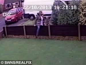 """CCTV grab shows Kirsty Robertson climbing over the fence neighbouring property of Mavis and Alan Ward. See Ross Parry Copy RPYHOUSE : A nightmare neighbour has been banned from contacting an elderly couple she harrassed for FOURTEEN years because she didn't like the colour of their bungalow.  Kirsty Robertson, 46, warned """"I won't stop until you're dead"""" as she made the lives of retired Mavis and Alan Ward a constant misery. A court heard they were forced to turn their 000 bungalow into a """"virtual fortress"""" and carry panic alarms in fear of what she might do next. Shocking CCTV footage showed Robertson climbing over their shared fence, pulling plant pots from their wall and throwing them on the floor. She then looked into the windows of Mr and Mrs Ward's bungalow in Thornton-Cleveleys, Lancs., shouting and pointing her finger."""