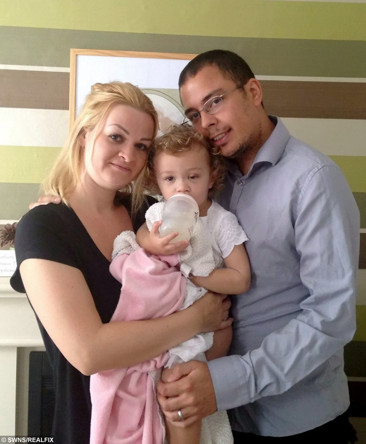 Poppy Cooper whose eye was injured on a hook on a clothing rail in Calvin Klein in Ashford, Kent - Pictured with mum Jenny and dad Ryan, post operation.  A distraught mother is sending out a safety warning after her toddler's eye was badly injured on a hook on the end of a clothing rail.  See MASONS story MNEYE.  Two-year-old Poppy Cooper needed surgery on her eyelid after the horrific accident, which took place at the Calvin Klein store, at the Ashford Designer Outlet, in Kimberley Way.  Days later, she is still unable to open her eye, which is swollen and very sore.  The accident happened on Saturday when Poppy, who was with her mum, dad Ryan and sister Emie, walked into the bottom row of rails, which were displaying underwear.  Her eyelid became stuck on the end of the hook and she started screaming immediately.  Poppy was eventually released and an ambulance was called.  She was taken to A&E at Ashford's William Harvey Hospital, where a scan revealed a cut inside her upper eyelid.  She stayed overnight and had surgery on Sunday.