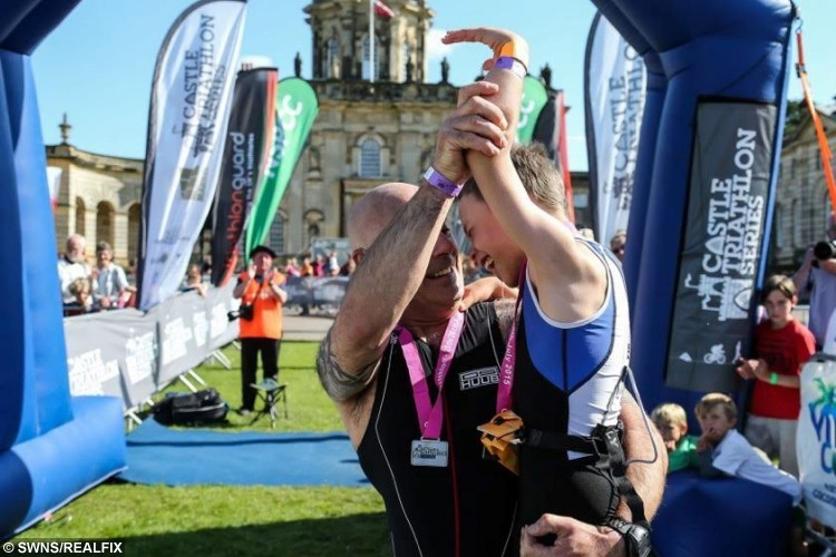 Bailey celebrates with his Dad Jonathan at the finishing line of the Castle Howard Triathlon. Bailey Matthews, 8, from Doncaster completed  his first ever triathlon. Bailey, who has cerebral palsy, but was cheered over the line by hundreds of emotional spectators after completing a 100m lake swim, 4,000m bike and 1,300m run at Castle Howard in Yorkshire. See Ross Parry copy RPYTRIATHLON 247 July 2015