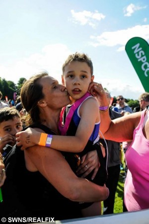 Bailey celebrates with his Mum Julie at the finishing line of the Castle Howard Triathlon. Bailey Matthews, 8, from Doncaster completed  his first ever triathlon. Bailey, who has cerebral palsy, but was cheered over the line by hundreds of emotional spectators after completing a 100m lake swim, 4,000m bike and 1,300m run at Castle Howard in Yorkshire/ See Ross Parry copy RPYTRIATHLON 247 July 2015