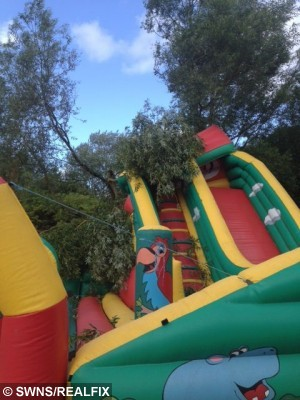 """The aftermath of the tree falling on a bouncy castle at Funland at Pennington Flash Country Park in Leigh. See Ross Parry copy RPYSAVE : A brave girl saved her three-year-old brother's life when a 40ft TREE fell on them as they played on an inflatable slide. Quick-thinking Sophie Parkinson, seven, dragged little Daniel to safety as he lay trapped beneath a pile of branches. They were sat on the top of the slide with their brother Alex when the tree trunk split in two and began to plummet towards the children.  Dad Mike who witnessed the freak accident at Funland in Leigh, Gtr Mancs., on Sunday, said: """"They were the only children on the slide and I took a picture of them at the top before walking back to sit on a bench to watch them come down."""