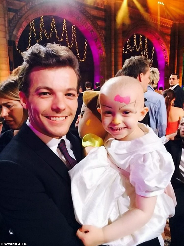 Collect picture of Chloe Balloqui with Louis Tomlinson from One Direction. One Direction's Louis Tomlinson meets his bravest fan yet - an adorable four-year-girl who is battling cancer for the second time. See NTI story NTICANCER:  Little Chloe Balloqui is always smiling despite her fight against Neuroblastoma, a child cancer of the nervous system, and her positivity has won the hearts of millions. And the poorly youngster was even happier than usual when she got to meet her 1D idol, who was hosting the Believe in Magic Ball for children with life-threatening illnesses. She beamed from ear to ear as the 23-year-old heartthrob held her in his arms and danced with her last Monday night (10/8).