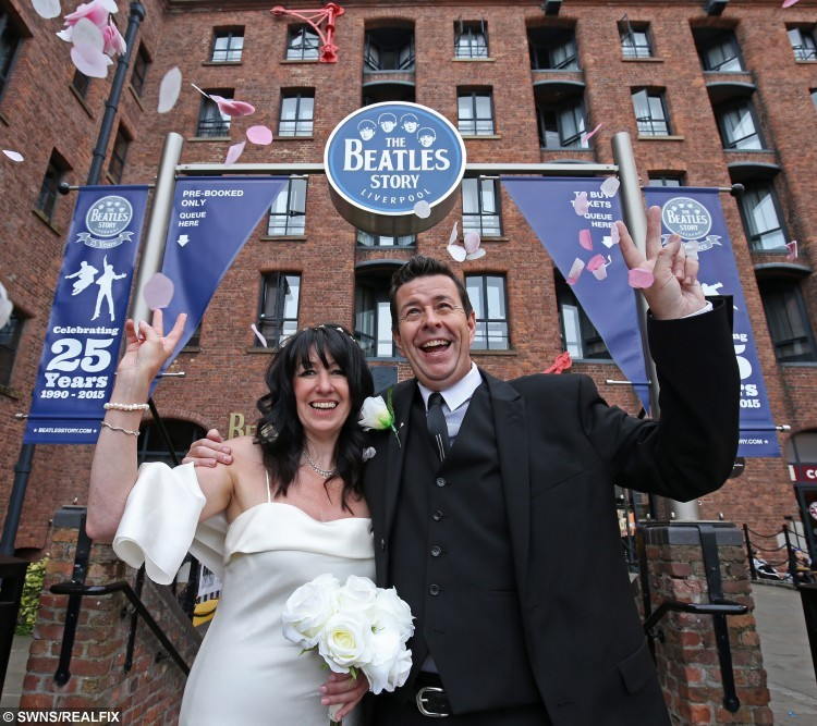 """Phil O'Connor weds his bride Julie Robinson at the Beatles Story Albert Dock Liverpool. The first ever wedding held at the venue a dream come true for the big Beatles Fans. See Ross Parry copy RPYWEDDING : This couple proved all you need is love when they became the first people to  wed at an attraction dedicated to the BEATLES.  Phil and Julie O'Connor, 50, tied the knot at The Beatles Story museum in Liverpool to mark their love for one another and the iconic rock band.  Their nuptials were held in the 'John Lennon White room' with a reception in its replica Cavern Club à reflecting the place where Phil popped the question. Security worker Phil, 49, said: """"We both grew up listening to Beatles music and we met thanks to a mutual connection with a Beatles tribute act.  """"One night I proposed to Julie on the stage of the Cavern Club in Liverpool and the rest is history."""