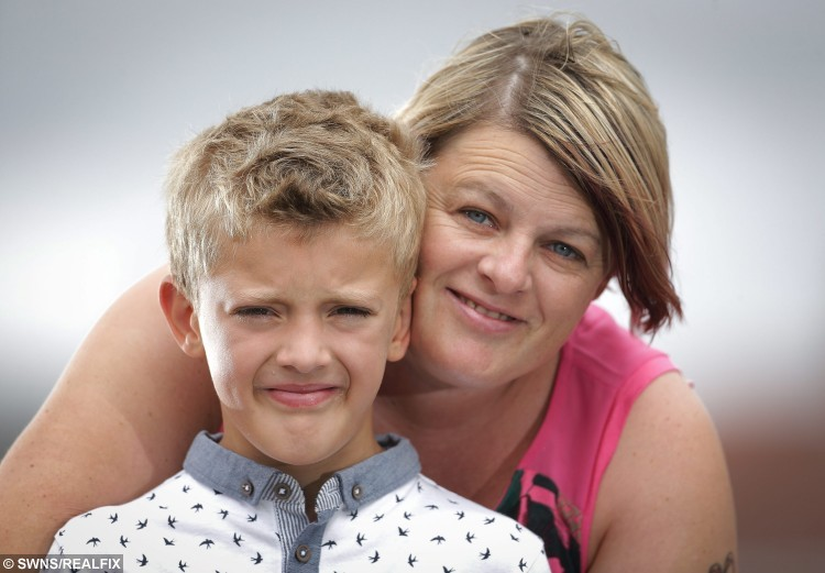 Daniel Booth 8 with mum Karen Booth of Barnsley today August  21 2015. Daniel has a card he hands out to members of the public who don't understand his ADHD. See Rossparry copy RPYCARD: An eight-year-old with autism and ADHD is explaining his behaviour to judgmental onlookers - by creating his own cards explaining his condition. Daniel Booth suffers from both attention deficit hyperactivity disorder and autism, which affect his behaviour when he is out in public. The youngster struggles to deal with change in his routine and quickly becomes upset when he hears onlookers mentioning his behaviour. One day Daniel approached his parents, Graham and Karen, asking them how he could explain to people why he acts as he does.  Tom Maddick / Rossparry.co.uk