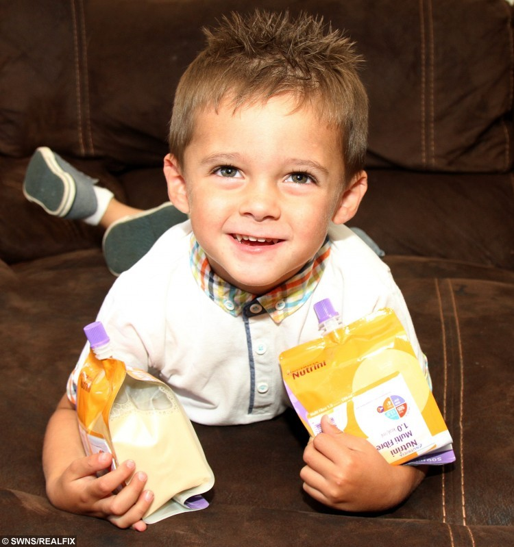 "Picture shows 3 year old Son Rhys who has a mysterious illness that means he can't eat or drink. See Ross Parry copy RPYEAT : A toddler has never eaten a meal in his life after being born with a mystery condition.  Little Rhys Leyland, three, was born without key signals in his brain that tell his body how to digest food.  He's the only child in the UK to be given a special pump that he can fill up himself - allowing food to enter his body through two tubes.  Mum Danielle Owens, who is Rhys' full-time carer, said: ""He is so clever for a three-year-old.  ""He has two feeding tubes, one in his bowels and one in his stomach. He is the only child in the UK that has this type of feeding tube."