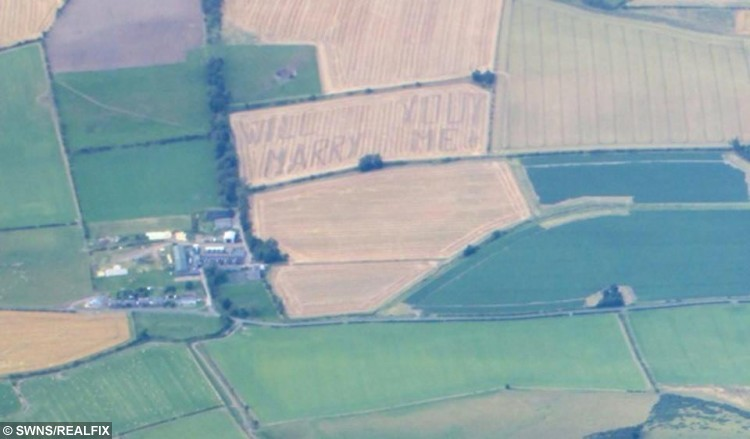 "An aerial view of the proposal ploughed into a field near Howtel in Northumberland by Andrew Gallon. See Centre Press story CPPROPOSAL; A romantic farmer took his girlfriend by surprise when he PLOUGHED his wedding proposal into a field. Creative Andrew Gallon, 24, rode a tractor across a meadow to create 10-ft letters spelling out the words ""will you marry me"". The father-of-one then blindfolded girlfriend Caroline Pymer, 26, and drove her up the hills before unveiling the message and popping the big question. Luckily, she agreed to be the farmer's wife and the lovebirds are now planning their big day."