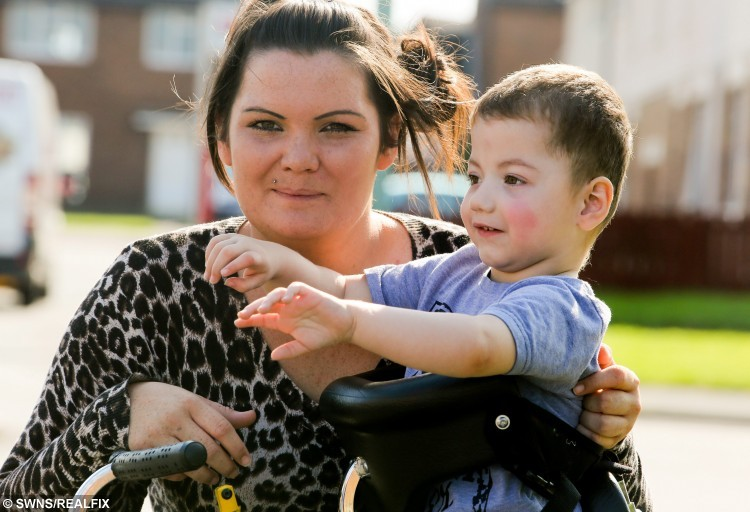 """Zac McCarthy, 2, from Sunderland who has a mystery condition which has baffled doctors in his walker he uses to get around outside. His mum Josene Pearson, 25, says he seems to """"live in his own bubble See SWNS story SWPOP; A toddler dubbed 'the boy in a bubble' who can't communicate with the outside world has baffled doctors and only responds to pop music - including MEAT LOAF. Zak McCarthy, aged two, cannot talk or walk unaided, has a phobia of food and his condition is so rare Britain's top medics are stumped. He shuns traditional children's toys, hates loud noises and cannot communicate with his parents at all. But his mum says they have found something the autistic lad responds to - he loves to listen to certain pop music."""