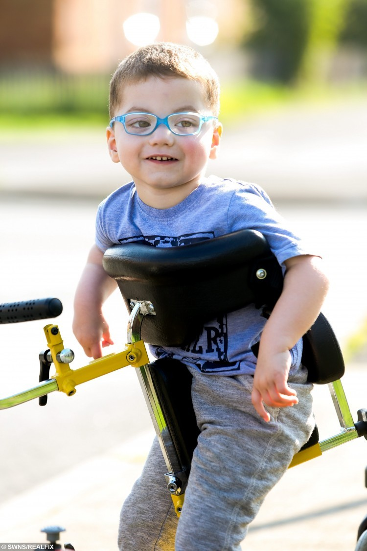 """Zac McCarthy, 2, from Sunderland who has a mystery condition which has baffled doctors in his walker he uses to get around outside. His mum Josene Pearson, 25, says he seems to """"live in his own bubbleSee SWNS story SWPOP; A toddler dubbed 'the boy in a bubble' who can't communicate with the outside world has baffled doctors and only responds to pop music - including MEAT LOAF. Zak McCarthy, aged two, cannot talk or walk unaided, has a phobia of food and his condition is so rare Britain's top medics are stumped. He shuns traditional children's toys, hates loud noises and cannot communicate with his parents at all. But his mum says they have found something the autistic lad responds to - he loves to listen to certain pop music."""