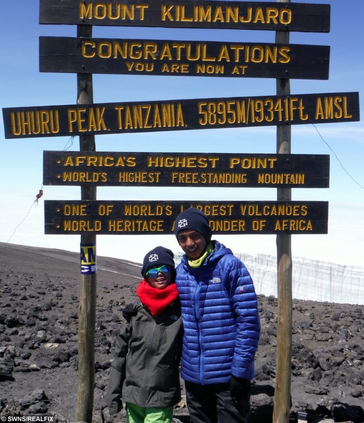 Seven year old Zain Ackrim (left), and his older brother Rehan pictured at the summit of Mt Kilimanjaro in Tanzania, which makes Zain the youngest ever Briton to reach the summit. See SWNS story SWCLIMB; A nine-year-old boy has become the youngest Brit ever to scale - mount KILIMANJARO. Intrepid Zain Ackrim hiked to the top  in over six days, crossing the finish line at 11.15am on August 8. It makes him the youngest Britain to climb Africa's highest peak in Tanzania with his 12-year-old brother, Rehan, and ten other people. Zain, from Holland Park, London, spent months preparing for the epic 5,895m climb which he made in just six days following a 12 hour final ascent.