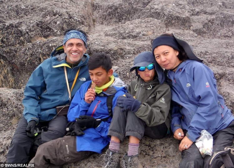 Seven year old Zain Ackrim (second right), his older brother Rehan and their parents Lindy and Raheel pictured during their ascent of Mt Kilimanjaro in Tanzania, which makes Zain the youngest ever Briton to reach the summit. See SWNS story SWCLIMB; A nine-year-old boy has become the youngest Brit ever to scale - mount KILIMANJARO. Intrepid Zain Ackrim hiked to the top  in over six days, crossing the finish line at 11.15am on August 8. It makes him the youngest Britain to climb Africa's highest peak in Tanzania with his 12-year-old brother, Rehan, and ten other people. Zain, from Holland Park, London, spent months preparing for the epic 5,895m climb which he made in just six days following a 12 hour final ascent.