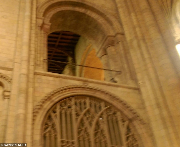 A woman visited a famously-haunted cathedral - and was astonished when she captured this creepy photograph of the ghost of a BISHOP. See SWNS story SWGHOST; Sales worker Kerry Launders, 29, went to Norwich Cathedral with partner Simon Tobb, 30, and her children Millie, two, and Oscar, one. She took lots of photos of the interior of the stunning 11th century building on her mobile phone camera. But it was not until she got home that she saw the shadowy figure in one of the images, staring down from an upper floor.