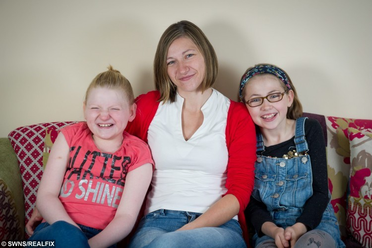 L-R Jessica Boyes, 11, with her mother, Kelly Boyes, 34, and sister, Keira Boyes, 9, at their home in Milton Keynes, 26th August 2015. Jessica Boyes who can't speak properly and suffers a string of health problems has a permanent smile on her face - due to a rare genetic condition.  See MASONS story MNSMILE; Jessica has a chromosome disorder which causes severe learning difficulties, epilepsy, poor eyesight, and sleeping problems   But the traits of Angelman syndrome, previously known as Happy Puppet Syndrome, also include frequent smiling and hand flapping when excited.  Children with the condition, which affects around one in 16,000, also tend to exhibit very sociable behaviour.