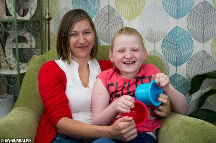 Jessica Boyes, 11, who suffers from Angelman syndrome with her mother, Kelly Boyes, 34, Milton Keynes, 26th August 2015. A girl who can't speak properly and suffers a string of health problems has a permanent smile on her face - due to a rare genetic condition. See MASONS story MNSMILE; Jessica Boyes has a chromosome disorder which causes severe learning difficulties, epilepsy, poor eyesight, and sleeping problems   But the traits of Angelman syndrome, previously known as Happy Puppet Syndrome, also include frequent smiling and hand flapping when excited.  Children with the condition, which affects around one in 16,000, also tend to exhibit very sociable behaviour.