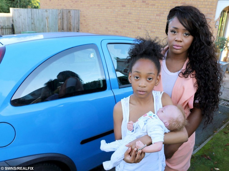 """Janaih Rattray (10) with the doll and her sister Delesia Rattray (20).  Police smashed their way into a car parked outside a Dudley hospital fearing a sick baby was locked inside - only to find the """"infant"""" was a doll.  See NTI story NTIDOLL.  The baby doll, named Ryan, had been left by its owner, 10-year-old Janaih Rattray, lying in a blanket on the front passenger seat of her sister Delesia's Vauxhall Corsa on the car park at Russells Hall Hospital while they visited their mother.  Janaih's family say they believe that observing the doll's hands, which they claim were visible in the car, it should have been possible for the officers to realise it was not real.  But police insist it was """"extremely life-like"""", with only the top of its head exposed, and the officers who smashed their way in genuinely believed it was a baby, alone and critically ill, in a locked car outside the hospital, which has a maternity unit."""