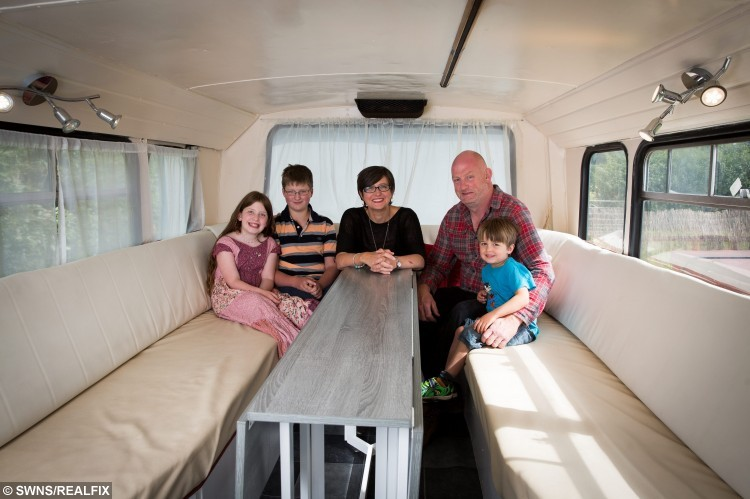 "Andrew and Lisa Jayne-Powis with thier children Charles, 13, Clara, 7 and George, 4 with the bus they have transformed into a holiday home.  A family sick of being rejected by cottages because of their big dogs, and too tall for caravans, bought a double-decker bus and turned it into a luxury holiday home.  See NTI story NTIBUS.  Andrew and Lisa Jane-Powis always struggled to find somewhere that would host them on their weekend adventures with their two Great Danes, Dean and Sauni.  With three lively kids and Andrew standing at 6ft 5in (1.95m), caravans had never been an option either for the outdoors loving family.  So four years ago they took the astonishing decision to buy a double-decker bus off Ebay, in the hope they could take it around Europe with their family.  But the Ã2,500 Leyland Atlantean just sat in the shed for three years, so the intrepid couple decided to transform the double-decker into an extravagant country retreat instead.  After six-weeks work and Ã15,000 later they began taking bookings for ""Betsy Blue"".  Betsy boasts three bedrooms on the top deck - one double, one bunk beds, and a single - and a fully equipped kitchen downstairs complete with a wood burner, as well as a hot tub outside."