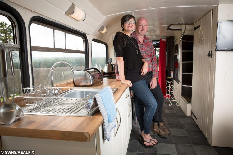 "Andrew and Lisa Jayne-Powis inside the bus they have transformed into a holiday home.  A family sick of being rejected by cottages because of their big dogs, and too tall for caravans, bought a double-decker bus and turned it into a luxury holiday home.  See NTI story NTIBUS.  Andrew and Lisa Jane-Powis always struggled to find somewhere that would host them on their weekend adventures with their two Great Danes, Dean and Sauni.  With three lively kids and Andrew standing at 6ft 5in (1.95m), caravans had never been an option either for the outdoors loving family.  So four years ago they took the astonishing decision to buy a double-decker bus off Ebay, in the hope they could take it around Europe with their family.  But the Ã2,500 Leyland Atlantean just sat in the shed for three years, so the intrepid couple decided to transform the double-decker into an extravagant country retreat instead.  After six-weeks work and Ã15,000 later they began taking bookings for ""Betsy Blue"".  Betsy boasts three bedrooms on the top deck - one double, one bunk beds, and a single - and a fully equipped kitchen downstairs complete with a wood burner, as well as a hot tub outside."