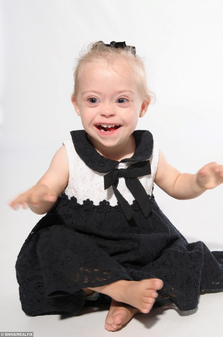 """Connie Rose Seabourne, aged 2, who was diagnosed with Down's Syndrome at her home in Morley, Leeds, West Yorkshire, on 3 September 2015. Pictured during a modelling shoot. See Ross Parry copy RPYMODEL : An adorable toddler with a special smile is aiming to be Britain's next TOT model after being snapped up by a casting agency. Little Connie-Rose Seabourne, who turns two in October and has been described as """"very cheeky"""" by her mum, wows people everywhere she goes with her wide eyes and happy face. Mum Julie Britton is incredibly proud of her beautiful daughter who is being put forward for commercial adverts in major shops and TV work. Connie-Rose was born two months premature but wasn't diagnosed with Down's Syndrome until she was two weeks old - something that didn't faze Julie, 42, or her partner Peter Seabourne, 44, at all."""