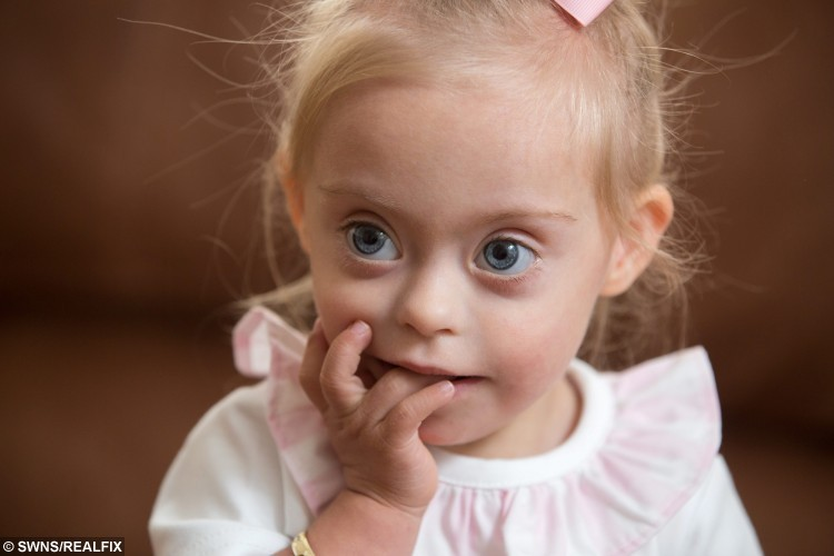 """Connie Rose Seabourne, aged 2, who was diagnosed with Down's Syndrome at her home in Morley, Leeds, West Yorkshire, on 3 September 2015. See Ross Parry copy RPYMODEL : An adorable toddler with a special smile is aiming to be Britain's next TOT model after being snapped up by a casting agency. Little Connie-Rose Seabourne, who turns two in October and has been described as """"very cheeky"""" by her mum, wows people everywhere she goes with her wide eyes and happy face. Mum Julie Britton is incredibly proud of her beautiful daughter who is being put forward for commercial adverts in major shops and TV work. Connie-Rose was born two months premature but wasn't diagnosed with Down's Syndrome until she was two weeks old - something that didn't faze Julie, 42, or her partner Peter Seabourne, 44, at all."""