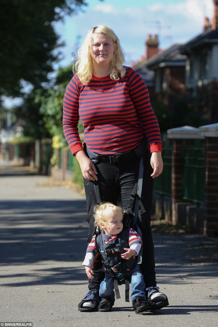 Francesca Ketley walking with her 16-month-old son Issac near their home in Hull, East Yorkshire. 21-year-old Francesca, who was told her young son may never walk, has been given a lifeline by a generous charity who has provided her with a special harness so he can walk on her toes. See Ross Parry copy RPYWALK. A mum who was told her young son may never walk has been given a lifeline by a generous charity who has provided her with a special harness so he can walk on her TOES. Francesca Ketley, 21, gave birth to 16-month-old Issac four weeks early and she became concerned about his developmental milestones after a few months.
