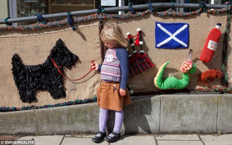"Four-year-old Monica Smith with knitted art in Selkirk.  Women from Selkirk, Ettrickbridge and Yarrow, in the Scottish Borders who are a team of ""guerrilla knitters"" have decorated local landmarks with crochet and knitted art. See Centre Press story CPKNIT. A 104 year old knitter who has Ãyarn bombedà her local town is thought to be the world's oldest street artist. Grace Brett is a member of a secret band of guerilla knitters, who have bedecked their town in artful knitting. Called the Souter Stormers, the group hit various landmarks in Selkirk, Borders, with their yarn work last week, following hours of preparation.  Members of the yarn bombing team are mainly over 60, but Grace à the oldest à has lived over a century."