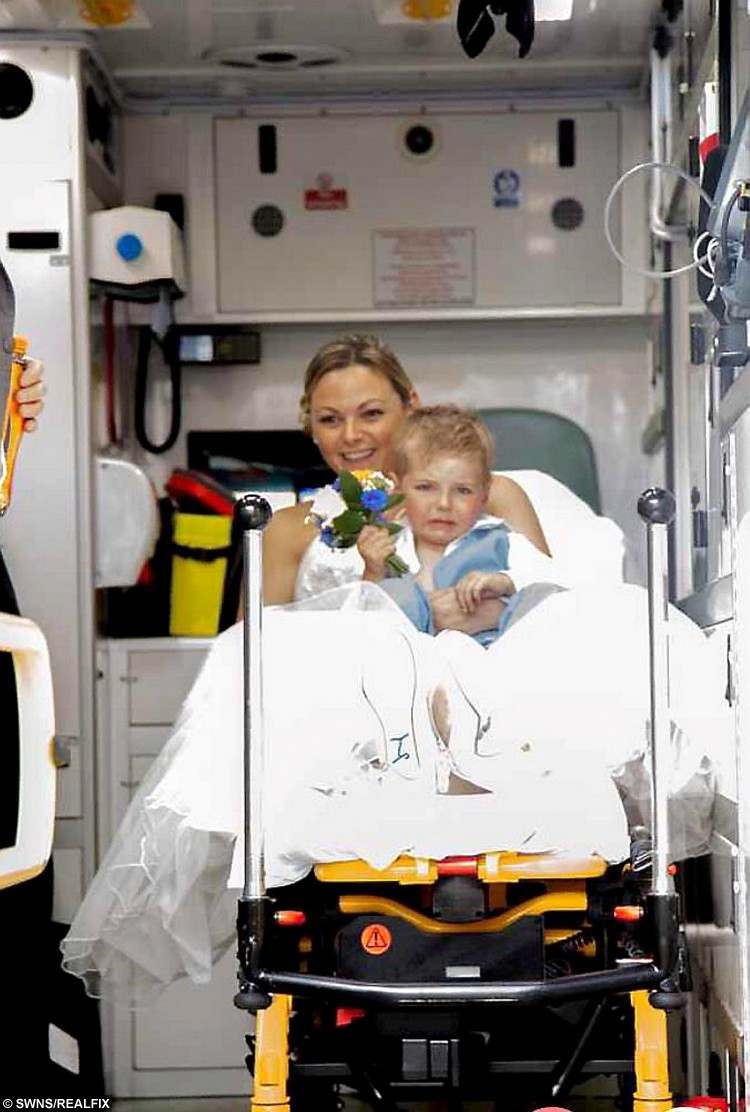 Please note mandatory credit Lucy Carnaghan / SWNS.com Little Freddie Coulton is treated in an ambulance as his mum Gemma holds him. See SWNS story SWBRIDE; A mum's dream wedding turned into a nightmare after she watched her three-year-old toddler fall à off a BALCONY. Gemma Coulton, 33, watched in horror as little Freddie fell ten feet through the balcony railings moments before her and partner Christopher Coulton were about to say their vows. The bride and her guests feared the worst when they heard the loud Ãthudà as son Freddie fell, abandoning any thoughts of the wedding. Gemma said: ÃMy three-year-old son fell through a gap in the balcony at Lewes Town Hall.