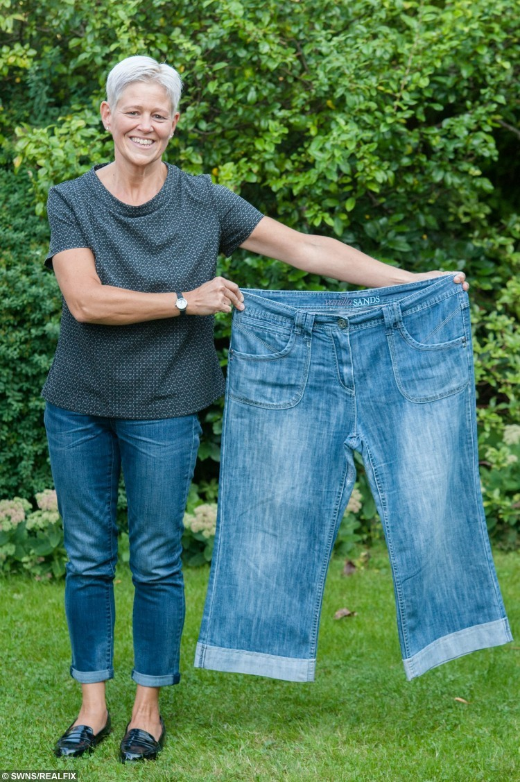 """Becky Peabody, 44, poses for a portrait with one of her old pairs of jeans at home in Street, Somerset, England. September 10 2015. Peabody lost weight after seeing a picture of herself in Ideal Home Magazine.  See swns story SWMAG. Designer Becky Peabody, 44, was delighted when Ideal Home magazine asked to feature her Victorian home. But she was mortified at how her 15 stone figure looked in the issue and was shamed into changing her fat-filled diet.Three years on Becky runs three times a week and swapped her baggy size 18 clothes for a stylish new size eight wardrobe. She said: """"I've always been overweight and always been on a diet of some kind, but when a picture of myself was printed in Ideal Home magazine for the all to see, I was nudged into taking action. """"One of my proudest moments, having my house featured in a glossy magazine, was dulled by the embarrassing photo of myself staring back from the pages. """"My mother was showing the photo to the world, and what should have been a lovely moment was 'oh my god, I look horrendous'. """"I knew I had to do something."""""""
