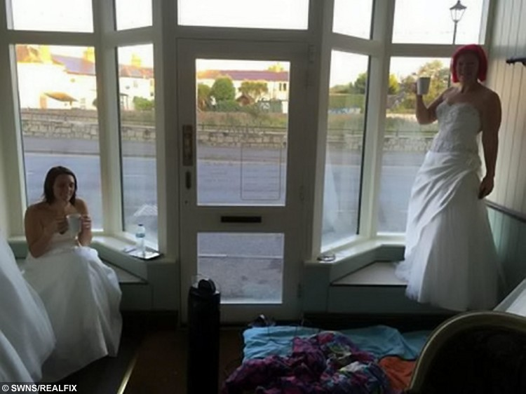 (L-R)  Tara Attis, 32, and Kate Holder, 27, drinking tea in the shop window of Budeiful Bridal, Bude, Cornwall. The women spent more than 50 hours dressed as mannequins in a shop window wearing bridal gowns - in a bid to win a dream wedding.  See SWNS story SWBRIDE; Determined Kate Holder and Tara Attis, 32, dressed as mannequins and stood on display in a 1ft x 3ft window space for two and a half days.  They stood still in Budeiful Bridal shop window with whoever could stay the longest winning a dream wedding.  Kate ending up the eventual winner after Tara finally stepped down late on Monday night after 58 and a half hours - with only the odd toilet break.