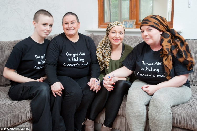 """(Left - right) Alexandra Downing, 23, Abi's friend, Julie Rounds, 46, Abi's mother, Abi Rounds, 23, and Ebony Rounds, 19, Abi's sister, pose for a portrait at Abi's home in Leominster, England. See SWNS story SWVIDEO; A young mum who was diagnosed with breast cancer aged just 22 broke the news to her family and friends - via a viral FACEBOOK video. Brave Abi Rounds, now 23, feared the worst when doctors told her she had two cancerous lumps last year but quickly decided she would """"kick cancer's butt"""". The stunning mum - who had watched her own mother and aunt fight the disease - was shocked by the diagnosis but wanted to let all her friends know at the same time. She made an online video breaking the devastating news to her pals, but vowing to do everything it takes to beat the disease with the support of her friends and family"""
