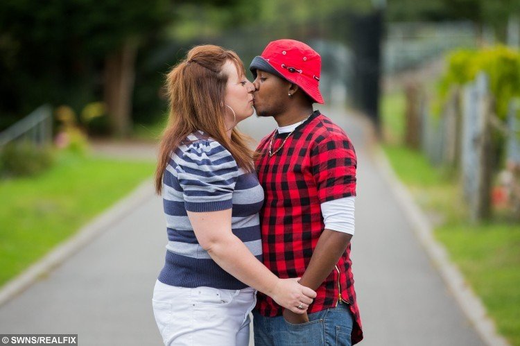 """Angharad Bullock, 38, and her husband Loric, 22, photographed at home in Swansea, Wales. See SWNS story SWTOYBOY; A British mum who got pregnant by her teenage Jamaican toyboy says their relationship is the """"real deal"""" - even though he gets mistaken for her daughter's BOYFRIEND. Telesales worker Angharad, 38, fell head over heels for Loric, then 19, after a friend set them up and they started chatting over Blackberry Messenger. After six months of talking on Skype, the mum went on a three-week holiday to Jamaica to meet her mysterious lover in the flesh - and fell pregnant with his child. Just weeks later, after saying """"I love you"""", Loric proposed via text - and Angharad said yes, so that he could secure a permanent visa to stay in the UK."""