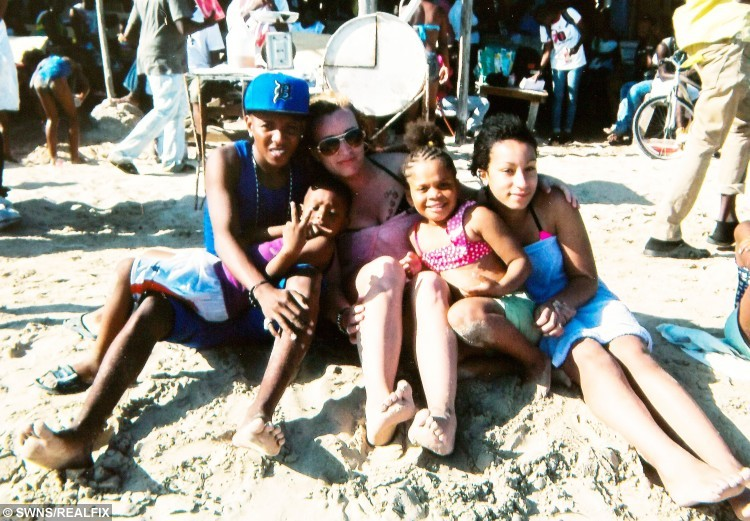 """Collect photograph of Angharad Bullock, and her husband Loric when they met in Jamaica, February 2012. Angharad's daughter Daisy is far right. See SWNS story SWTOYBOY; A British mum who got pregnant by her teenage Jamaican toyboy says their relationship is the """"real deal"""" - even though he gets mistaken for her daughter's BOYFRIEND. Telesales worker Angharad, 38, fell head over heels for Loric, then 19, after a friend set them up and they started chatting over Blackberry Messenger. After six months of talking on Skype, the mum went on a three-week holiday to Jamaica to meet her mysterious lover in the flesh - and fell pregnant with his child. Just weeks later, after saying """"I love you"""", Loric proposed via text - and Angharad said yes, so that he could secure a permanent visa to stay in the UK."""