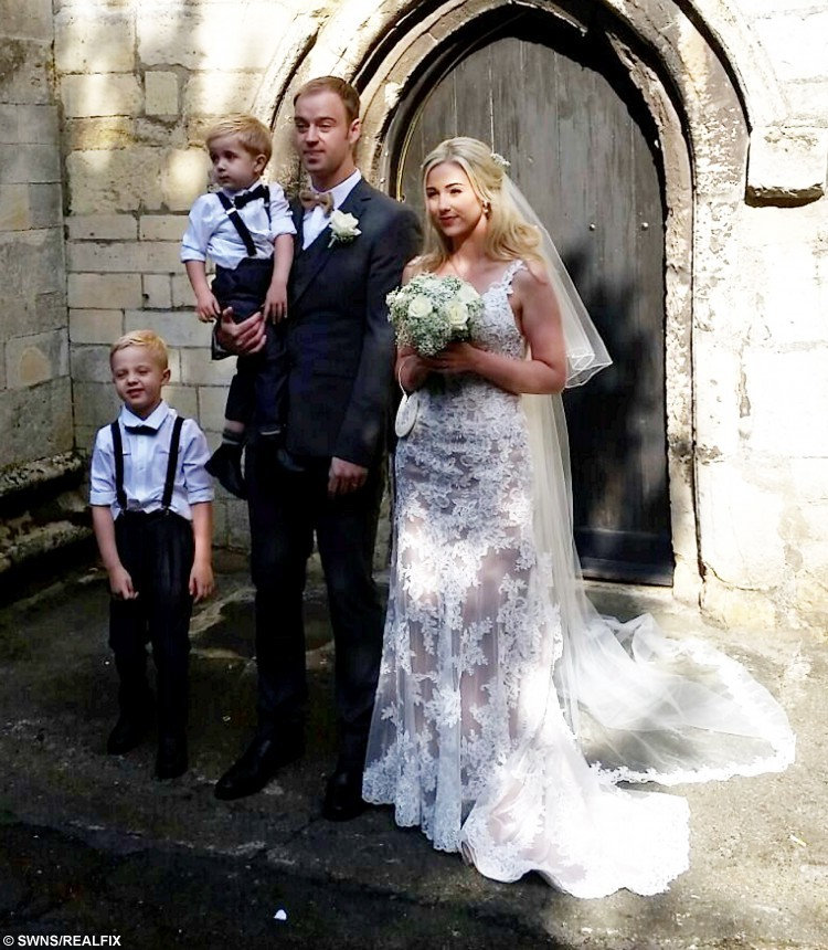 Emma Scarborough and her husband Jamie on their wedding day. See SWNS story SWSELFIE; A bride was delighted when the vicar at her wedding unexpectedly interrupted the ceremony - to take a SELFIE. Emma Scarborough, 26, had just met her husband-to-be Jamie, 28, at the head of the church when the vicar said he had something to do before he married them. Vicar Paul Frost pulled out a selfie stick and much to the amusement of the guests at St John's Anglican church snapped an amazing photo of the grinning wedding party. It is thought to be the first ever vicar wedding selfie using a selfie stick.