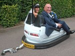 Newlyweds arrive at their reception in a fairground dodgem!