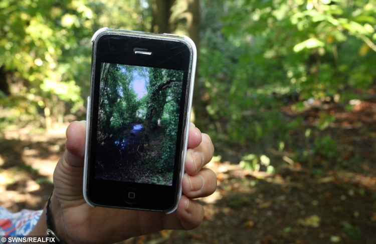 WEST BROMWICH, WEST MIDLANDS, 04/10/2015 Pensioner Elaine Stewart aged 65 from West Bromwich, West Midlands, has taken a picture on her phone of what she believes is a ghost. Elaine was walking through Sandwell Valley and stopped to take a picture of the woodland scene. It was only later when she was home and viewing the photos, that she made the discovery. Elaine believes the image is of a boy in 18th century attire, possibly a victim of the mine shafts that once ran underneath the site. the image in a clearing close to Wasson Pool, an area that has been a notorious haunted spot for decades . See NTI story NTIGHOST; A great-great gran was left spooked when she took a picture of a beauty spot and captured this eerie snap of an 18th century child ghost. Shocked Elaine Stewart, 65, was taking a woodland walk when she took a picture on her iPhone 3 but only discovered the scary image when she returned home. The picture, taken in Wasson Pool, in the Black Country last month, appears to show the outline of a boy wearing 18th century clothes leaning against a tree. Retired auxiliary nurse Elaine, from West Bromwich, West Mids., has researched the area and discovered the woodland is on the site of an 18th century coal mine.