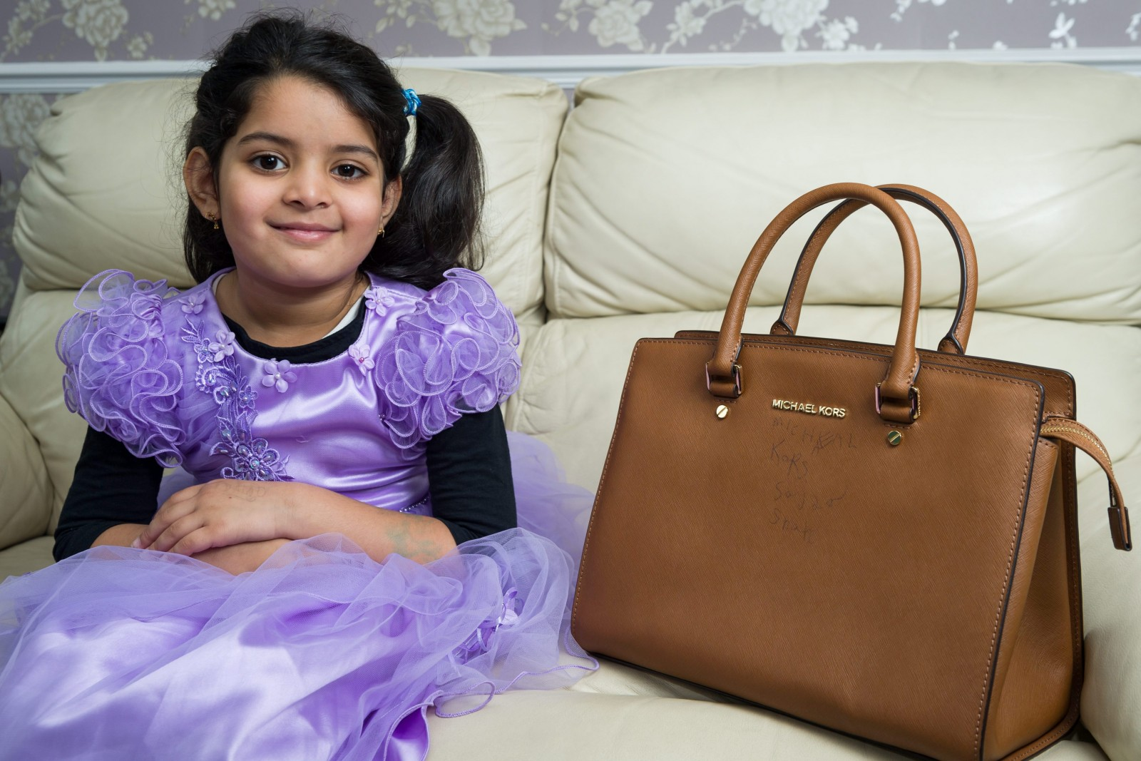 Five-year-old practises her handwriting… on her mum's designer handbag!