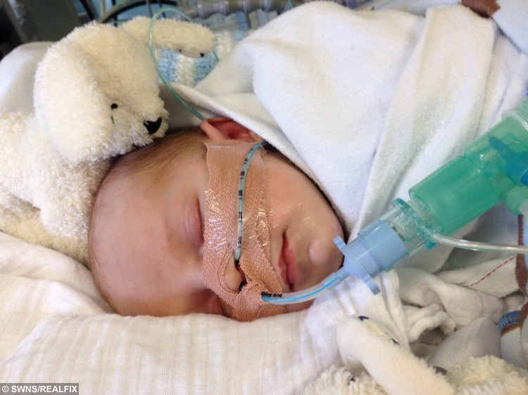"""Little Charlie Reynolds pictured in hospital shortly after his birth. See SWNS story SWBABY: A mum and dad long to be woken in the night by their screaming newborn - because a rare condition has left a youngster unable to laugh or CRY. Charlie Reynolds was born with a rare condition called vocal cord palsy, which affects only 200 babies in the UK every year. The four-month-old was born in May to parents Sophie, 26, and Scott, 31, but needed resuscitation after he struggled to breathe - which has left him unable to make a sound. Mum-of-two Sophie said: """"Now he can't make a sound - we long for him to wake us up in the middle of the night, but he's our silent little angel."""""""