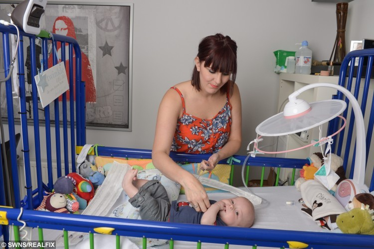 """Charlie Reynolds with his mother Sophie. See SWNS story SWBABY: A mum and dad long to be woken in the night by their screaming newborn - because a rare condition has left a youngster unable to laugh or CRY. Charlie Reynolds was born with a rare condition called vocal cord palsy, which affects only 200 babies in the UK every year. The four-month-old was born in May to parents Sophie, 26, and Scott, 31, but needed resuscitation after he struggled to breathe - which has left him unable to make a sound. Mum-of-two Sophie said: """"Now he can't make a sound - we long for him to wake us up in the middle of the night, but he's our silent little angel."""""""