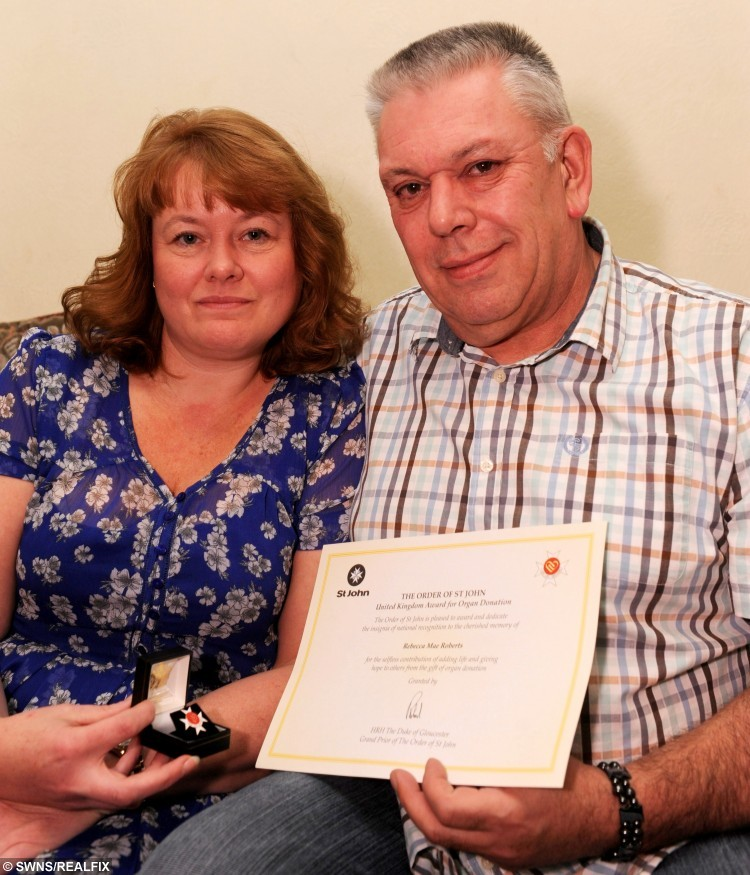 """Geoff and Tracy Roberts with the certificate and medal they were presented to honour their decision to donate organs from their late daughter Rebecca Mae Roberts. See Ross Parry story RPYDONOR: A teenager who tragically died after suffering an epileptic seizure has been honoured after her organs saved the lives of SIX people. Becky Roberts was just 17 when she passed away in March this year. Now the brave youngster, from Scunthorpe, North East Lincs., has been given a posthumous award from St John Ambulance with the words """"add life, give hope"""". Becky's mother, Tracy Roberts, spoke proudly of her """"bright and funny"""" daughter."""