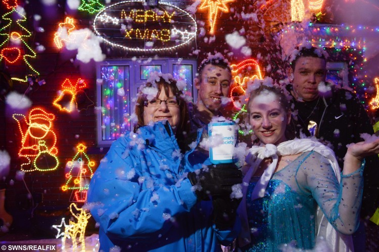 Stuart Bizley and his partner Shaun Duval light up their house with over 1700 lights this Christmas - also pictured are Julie Kemp from the Alzheimer's Society and Elsa from Frozen. See SWNS story SWLIGHTS; It might still be November but this house has already gone Christmas crazy - after being covered in 4,000 fairy lights. Stuart Bizley, 22, loves the festive season and spends the entire year buying new light fittings, sparkling reindeer and illuminated Santas. The care assistant - who strings up 1,700 lights on the roof alone - reckons the illuminations cost Ã10,000 to buy, with the electricity bill coming to Ã10 a day. He is so proud of the display, which takes two months to set up, he hosted an official lights switch-on ceremony for his neighbours in Knowle, Bristol, on Saturday.
