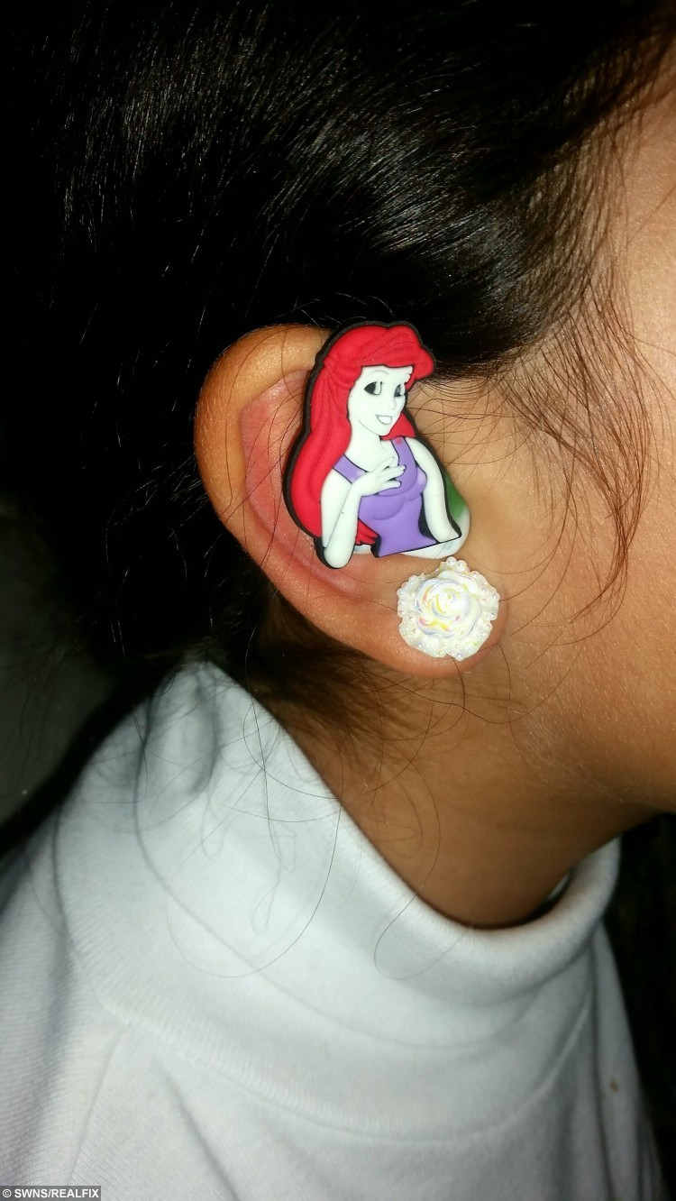 """Collect photo of Ariel from The Little Mermaid cartoon hearing aid cover. See SWNS story SWHEAR; A mum has helped her deaf son beat the bullies by putting colourful cartoon covers - on his HEARING AIDS. Little Santiago Lozada was diagnosed with deafness earlier this year after having trouble concentrating at school and ordered to wear two hearing aids. Nathalie Lozada, 32, was horrified when she realised her five-year-old son was being teased at school because of his new hearing aids, which he hated wearing, so she decided to stick his favourite cartoon characters on the sides. Nathalie, a deputy nursery nurse, said: """"He was given hearing aids but associates them with his school uniform so doesn't like to wear them."""""""