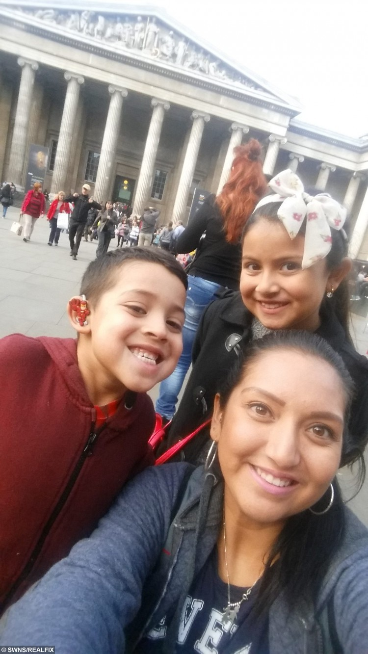 """Nathalie Lozada (front) from Brixton, south east London with her son, Santiago, and daughter Aisha. SWNS story SWHEAR; A mum has helped her deaf son beat the bullies by putting colourful cartoon covers - on his HEARING AIDS. Little Santiago Lozada was diagnosed with deafness earlier this year after having trouble concentrating at school and ordered to wear two hearing aids. Nathalie Lozada, 32, was horrified when she realised her five-year-old son was being teased at school because of his new hearing aids, which he hated wearing, so she decided to stick his favourite cartoon characters on the sides. Nathalie, a deputy nursery nurse, said: """"He was given hearing aids but associates them with his school uniform so doesn't like to wear them."""""""