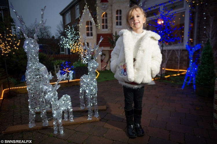 Phoebe Crowson age 6 standing by Mick Bells Christmas display in Stamford, Lincolnshire. Mick Bell age 60 has been decorating the front of his of his house in Stamford for the past 30 years and each year it grows a little bigger. See MASONS story MNLIGHTS.  Mick collects money for charity each year and  this year he is collecting for the Phoebe Research fund. Phoebe Crowson age 6 from Stamford has the rare genitic skin condition Recessive Dystrophic Epidermolosis Bullosa or EB for short. this condition a lifelong condition in which the skin is fragile and will blister or shear away with minimal friction and trauma, it also affects other mucosae such as eyes, mouth oesophagus, causing painfull blistering and scarring as healing occurs. There is no cure and treatment is symptomatic.