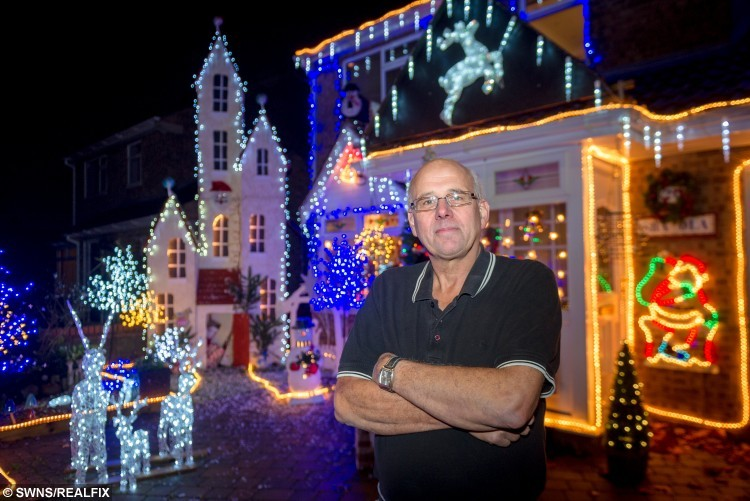 Mick Bell with his Christmas display in Stamford, Lincolnshire. Mick Bell age 60 has been decorating the front of his of his house in Stamford for the past 30 years and each year it grows a little bigger. See MASONS story MNLIGHTS.  Mick collects money for charity each year and  this year he is collecting for the Phoebe Research fund. Phoebe Crowson age 6 from Stamford has the rare genitic skin condition Recessive Dystrophic Epidermolosis Bullosa or EB for short. this condition a lifelong condition in which the skin is fragile and will blister or shear away with minimal friction and trauma, it also affects other mucosae such as eyes, mouth oesophagus, causing painfull blistering and scarring as healing occurs. There is no cure and treatment is symptomatic.