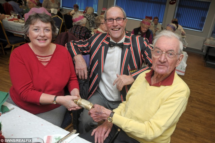 "Julie Rolling with Reg Bennetts of Camborne RFC and Peter Campbell at the Camborne Rugby Club Christmas dinner which was paid for by kind hearted solicitor Peter Campbell. See SWNS story SWLUNCH; A kind-hearted pensioner treated 50 strangers to a slap-up Christmas dinner at his local rugby club to ensure they were not alone over the festive period – and footed the £2K BILL. Retired solicitor Peter Campbell, 87, paid for the festive feast for people in his local community who would otherwise be spending the festive period alone. Generous Peter booked out his local rugby club in Camborne, Cornwall, and laid on a platter of turkey and wine, and he footed the £2,000 bill. Peter was ceaselessly thanked for his efforts, and now he intends to make the meal an annual tradition, and he said he will continue to do the event ""as long as I've got air in my lungs""."