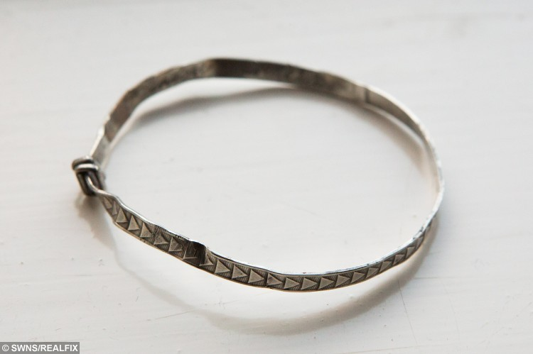 Lindsey Pollastrone's bracelet which she has been reunited with more than 40 years after it was lost. Chippenham, Wiltshire. 01 December 2015. See SWNS story SWRETURN; A woman has been reunited with her childhood christening bracelet more than FORTY years after she lost it in a field as a child. Lindsey Pollastrone, 48, was given the silver heirloom by her parents in 1974 when she was seven-years-old and wore it every day. She was heartbroken when she lost it months later as she played in a field and after moving house gave up hope of ever seeing it again. But last month metal detectorists dug up the bangle in a field in Charfield, South Glos., and launched an online appeal to find its rightful owner.